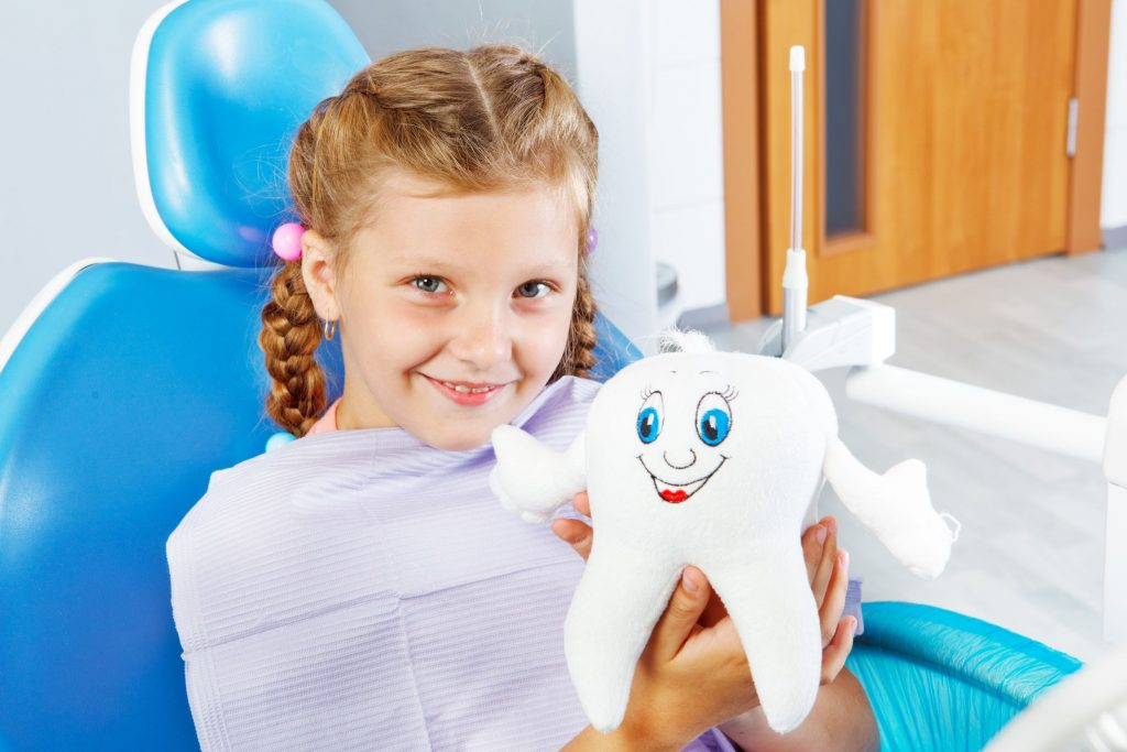 cheerful child in dentist seat holding a toy tooth