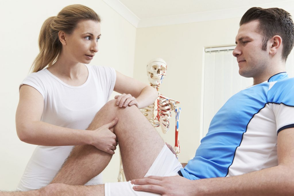 osteopath giving ultrasound treatment to male client with sports injury