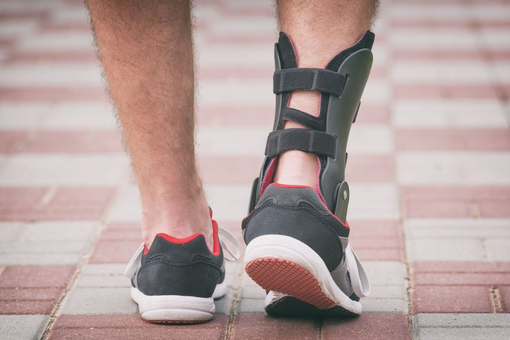 man in athletic sneakers wearing ankle orthosis or brace