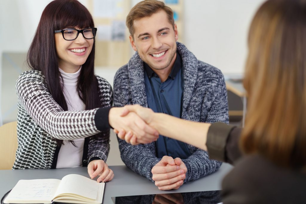 couple shaking hands with their broker or insurance agent in her office smiling happily as they close a deal