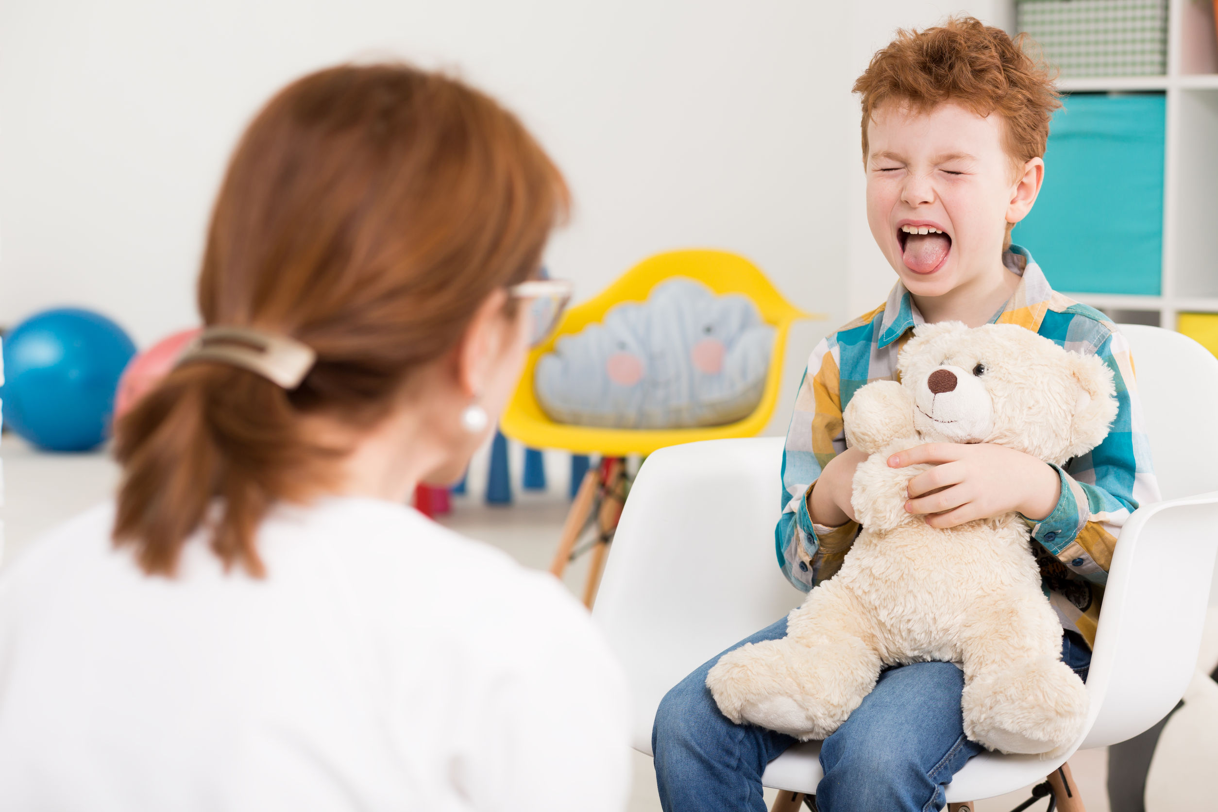 naughty young boy with adhd screaming at psychologist's office
