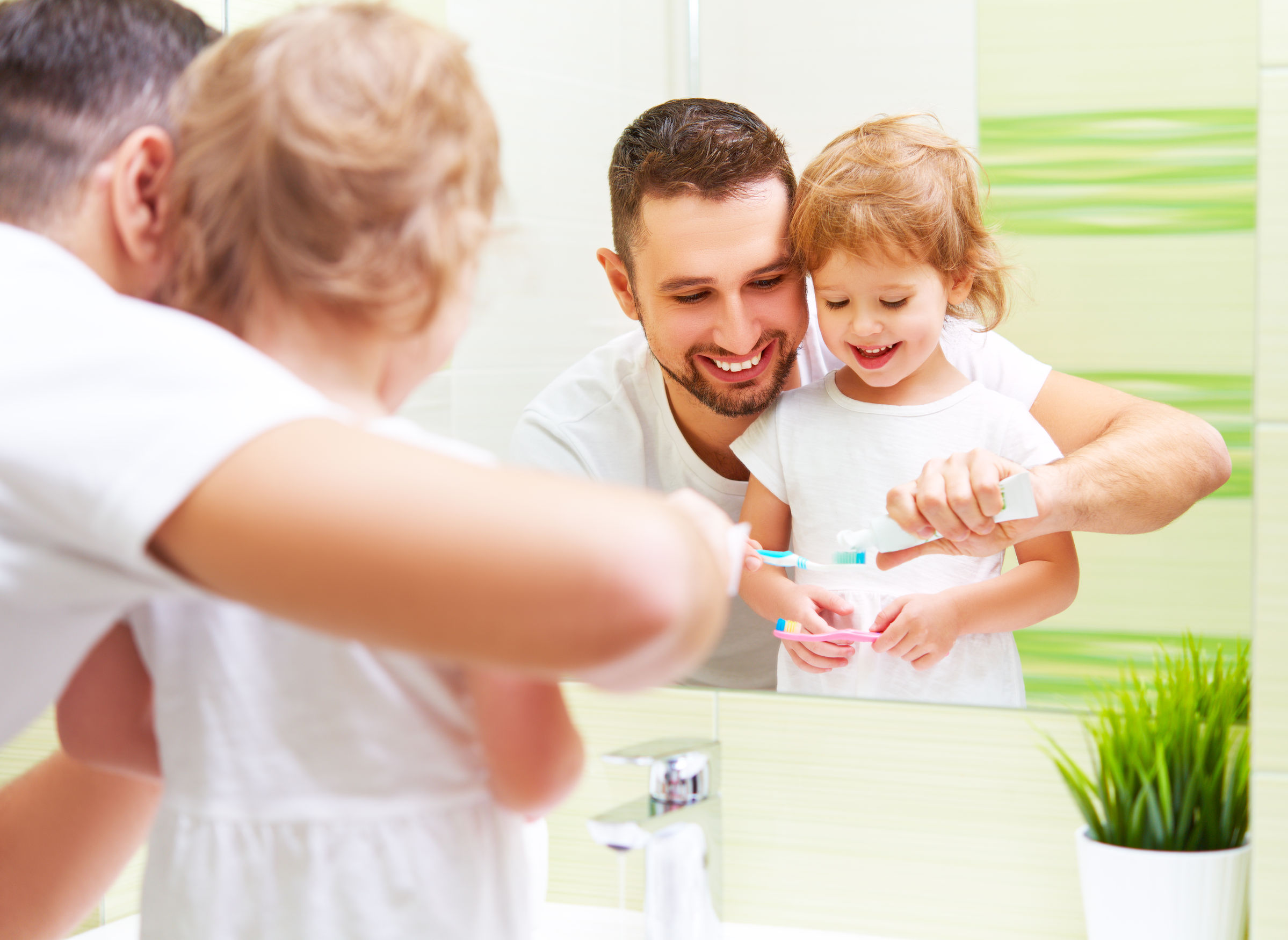 happy family father and daughter child girl brushing her teeth in the bathroom toothbrushes