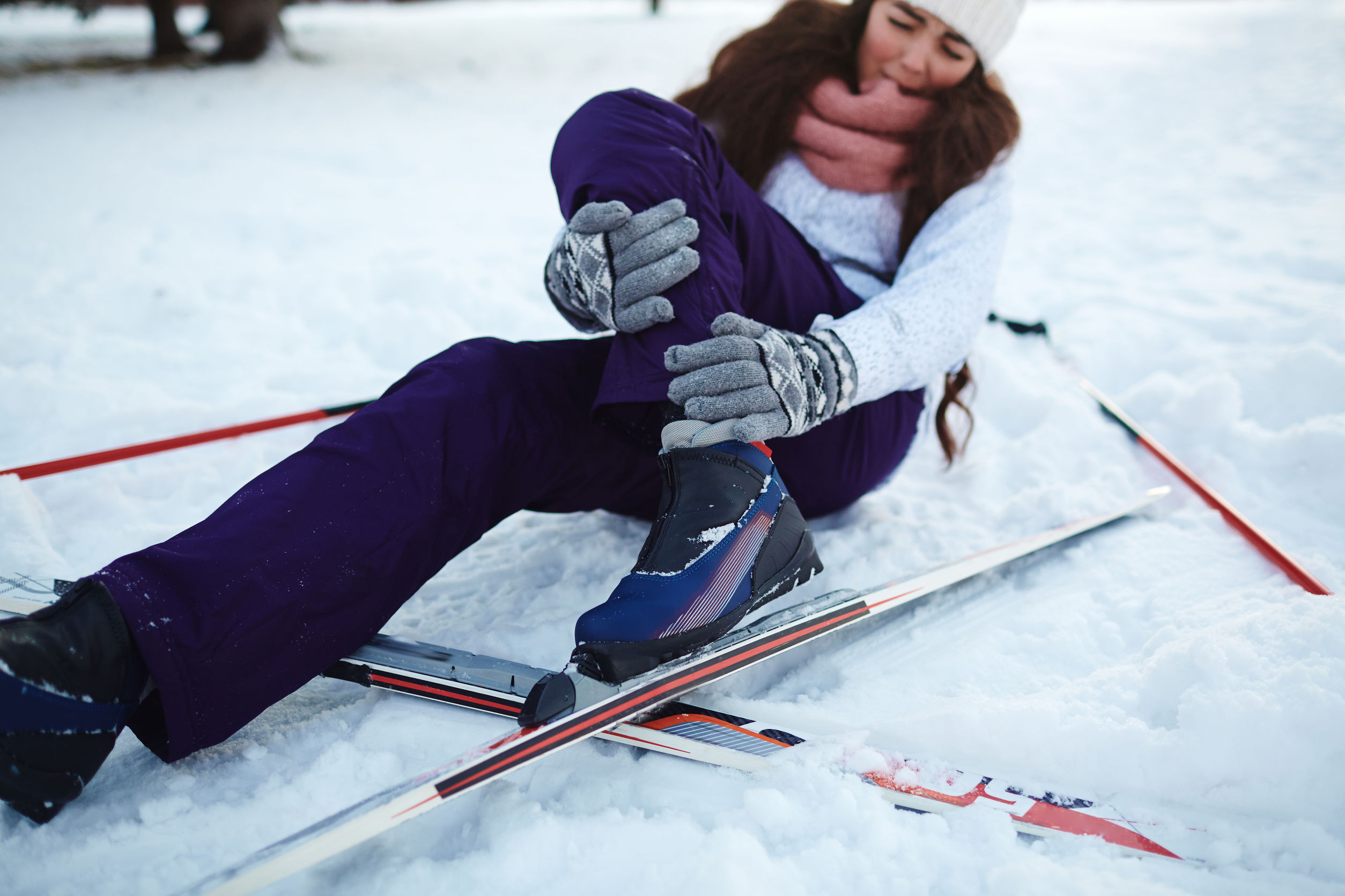 active female fell down on snow during ski training
