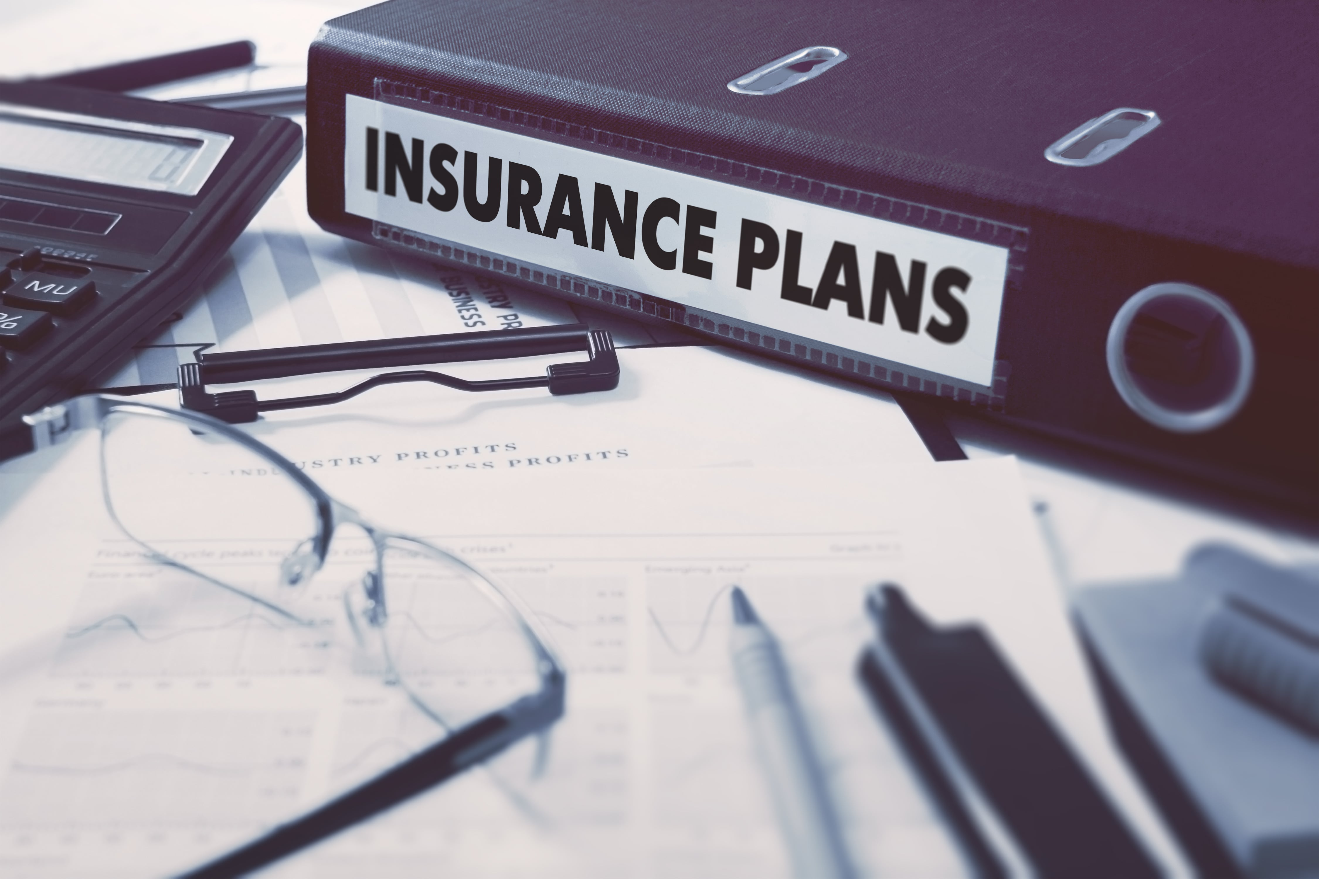 insurance-plans-ring-binder-on-office-desktop-with-office-supplies-business-concept-on-blurred-backg