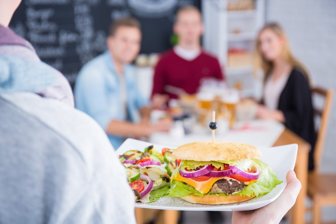 person-holding-white-plate-with-cheeseburger-and-salad