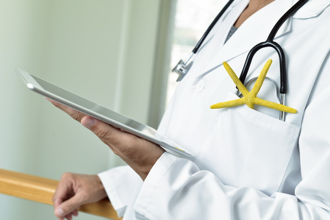 doctor-man-using-a-tablet-with-a-colorful-yellow-starfish-and-a-stethos