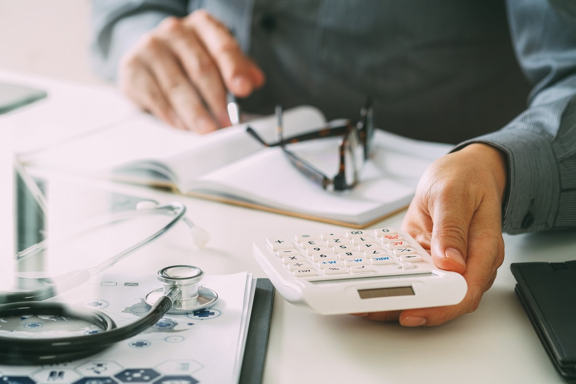 healthcare-costs-and-fees-concept-hand-of-smart-doctor-used-a-calculator-for-medical-costs-in-modern