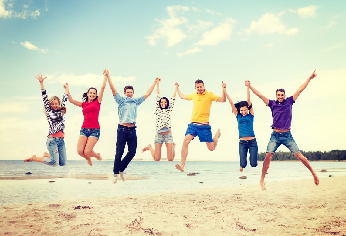 summer-holidays-vacation-happy-people-concept-group-of-friends-jumping-on-the-beach