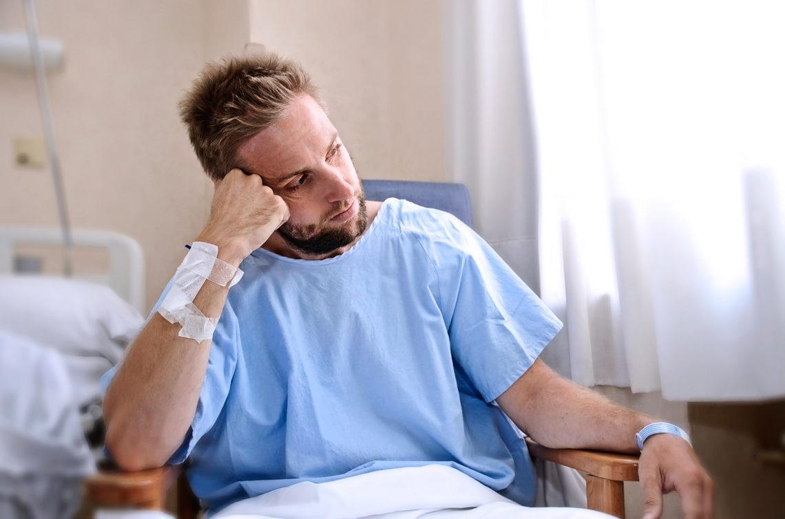 young-injured-man-in-hospital-room-sitting-alone-in-pain-looking-negative-and-worried-for-his-bad