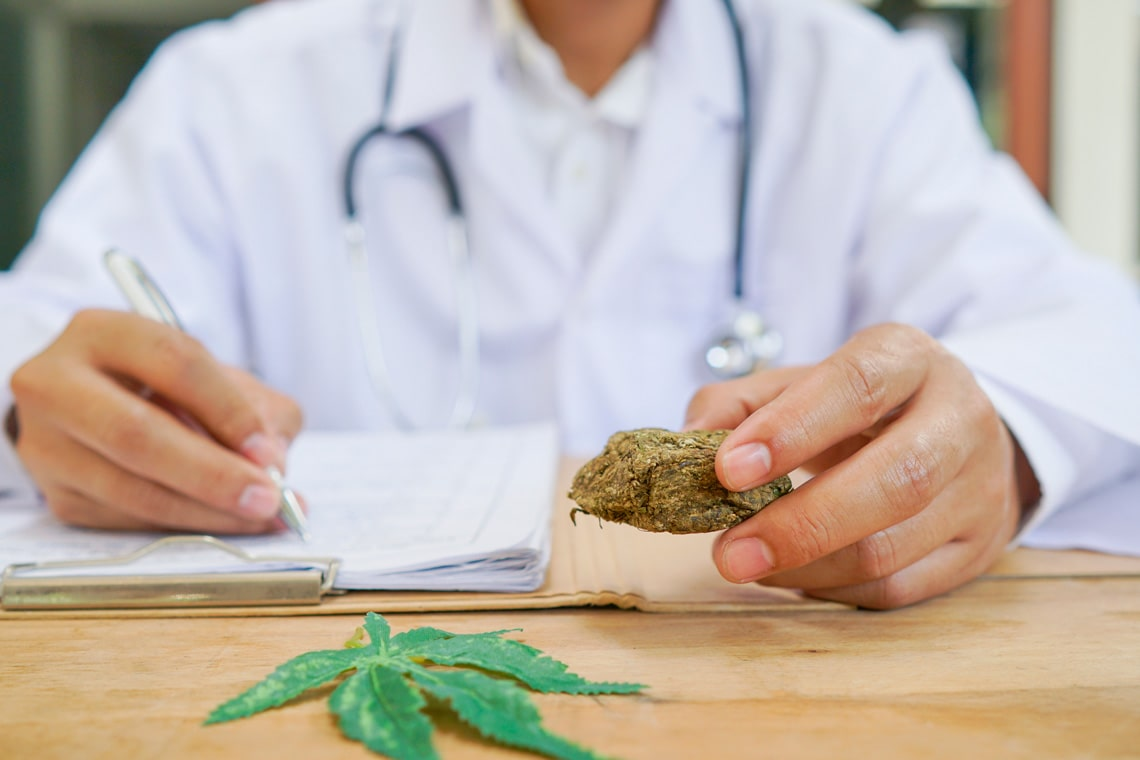 doctor-writing-on-prescription-blank-and-bottle-with-medical-cannabis-on-table-close-up