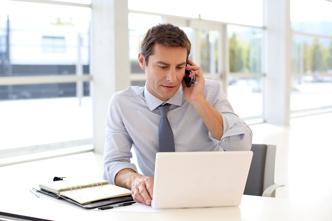 portrait-of-businessman-talking-on-mobile-phone-in-office