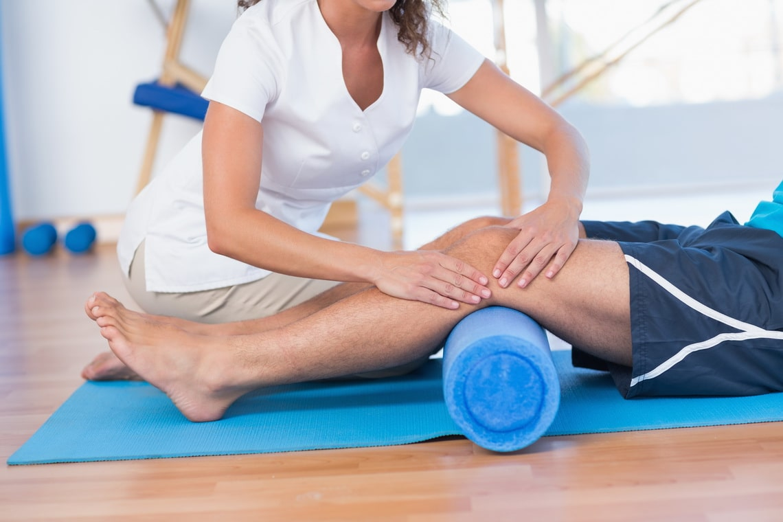trainer-working-with-man-on-exercise-mat-in-fitness-studio